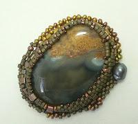 брошь из натурального камня, оплетенного бисером